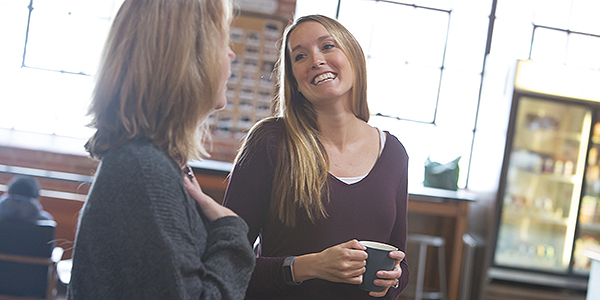 Two women talking as one smiles and holds a coffee cup.